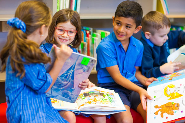 Students smiling and reading books in school library