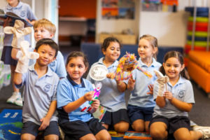 Students playing with puppets in colourful school library