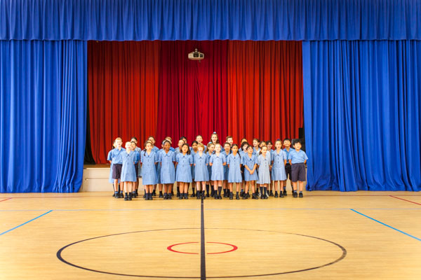 Students singing in front of a stage with a bright blue and red backdrop