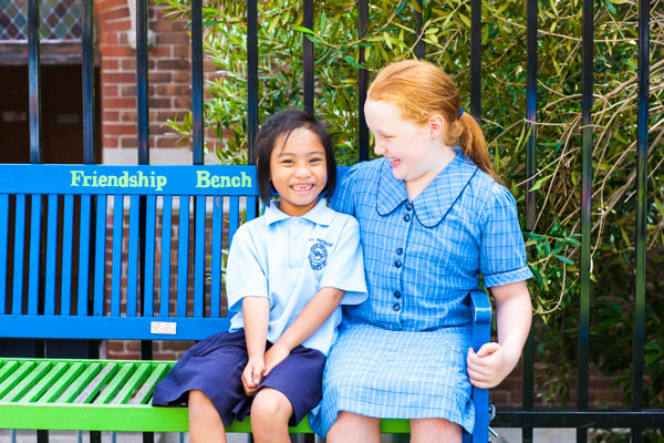 Year 6 and Kindy student sitting on a bench chatting