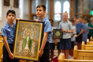 Students carrying framed artwork of St Patrick in a church procession