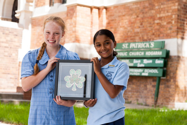 Two students smiling and holding up framed artwork of a shamrock