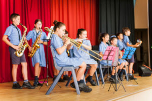 Student band playing instruments on stage